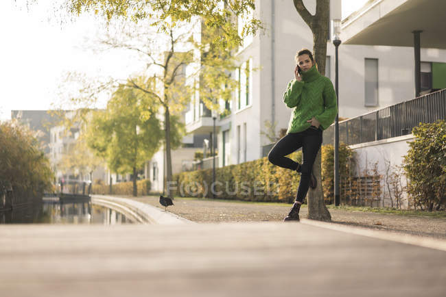 Жінка по телефону носити зелений Пуловер з водолазкою і спираючись на стовбур дерева — стокове фото
