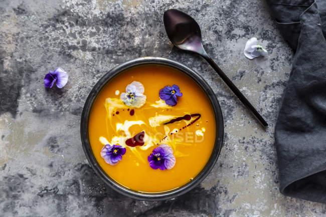 Bacia de sopa de abóbora creme decorada com flores comestíveis — Fotografia de Stock