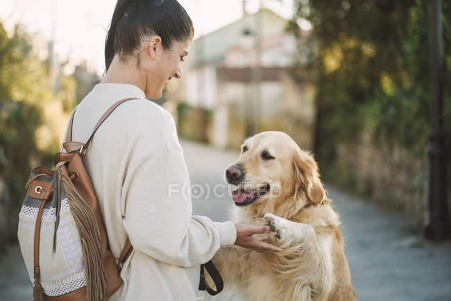 Jeune femme heureux jouant avec son chien de retriever d'or à l'extérieur — Photo de stock