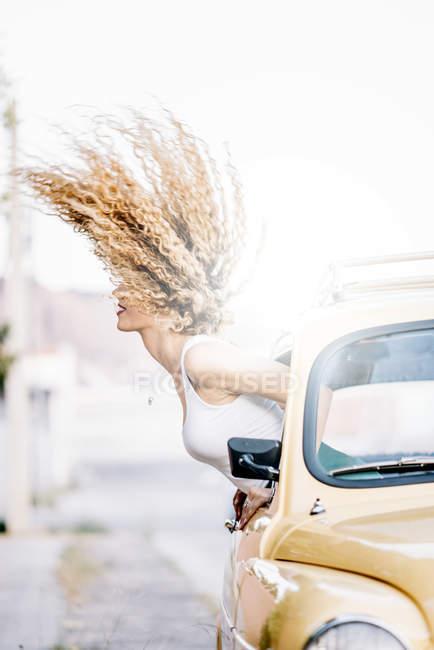 Jovem mulher se inclinando para fora da janela do carro e jogando seu cabelo — Fotografia de Stock