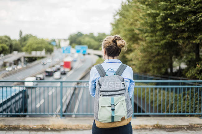 Rear view of woman with backpack on motorway bridge — Stock Photo