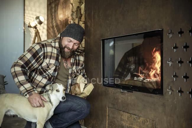 Бородатый мужчина с собакой у камина дома, человек, держащий дрова — стоковое фото