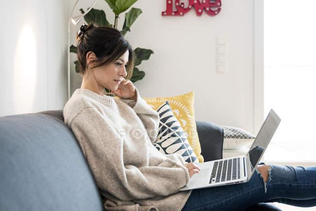 Mujer sentada en su sofá, navegando por la red, usando un portátil - foto de stock