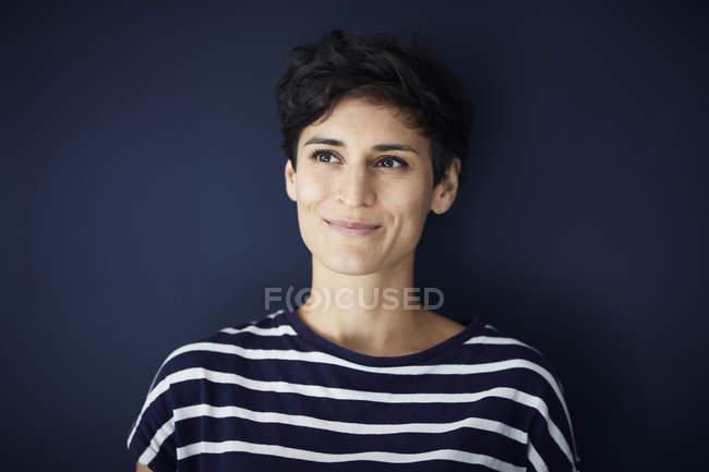 Портрет усміхнена жінка на синьому стіні — стокове фото