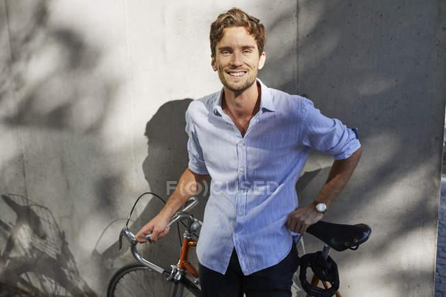Портрет улыбающегося молодого человека с гоночным циклом перед бетонной стеной — стоковое фото