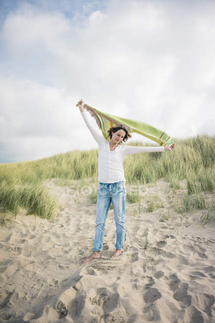 Mature woman holding flapping scarf in the wind, relaxiang in the dunes — Stock Photo