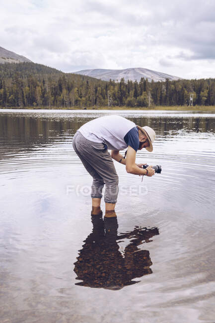 Sweden, Lapland, man standing in water taking photos — Stock Photo