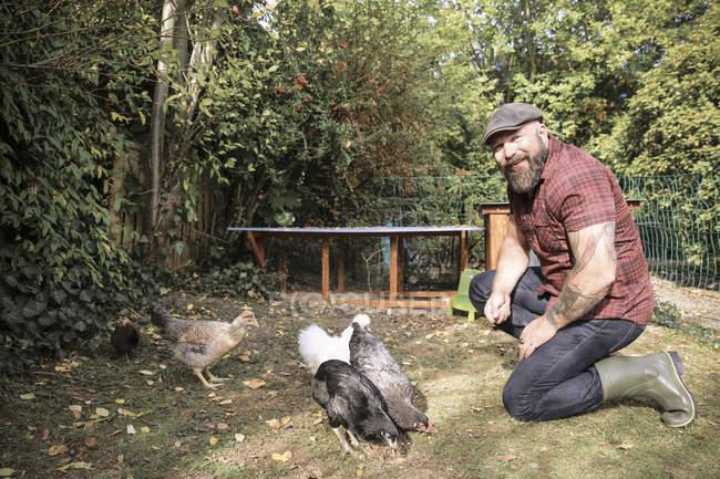 Bearded Man in own garden feeding range chickens — Stock Photo