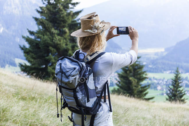 Germany, Bavaria, Oberammergau, young woman hiking taking a cell phone picture on mountain meadow — Stock Photo