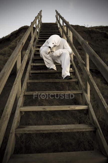 Mann im Eisbärkostüm auf Stufen, Verzweiflung und einsam trauriger Charakter — Stockfoto