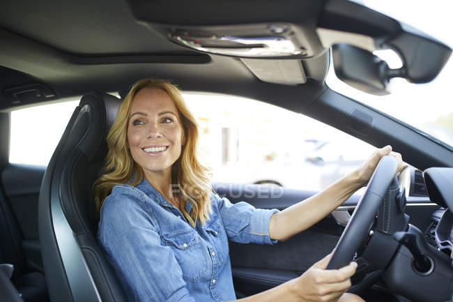 Smiling woman driving car — Stock Photo