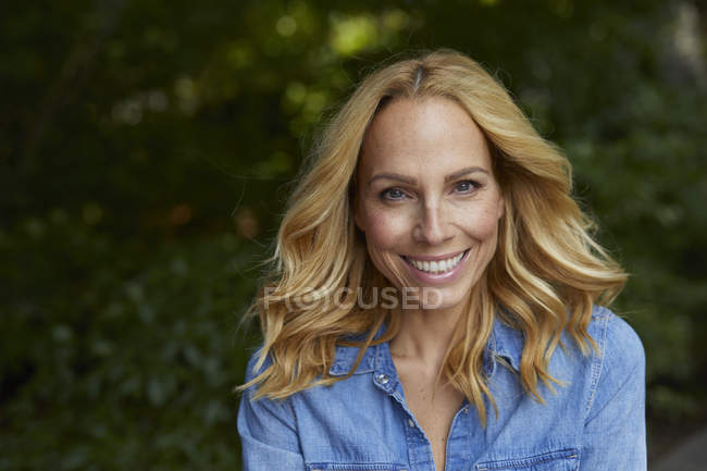 Portrait of smiling blond woman outdoors — Stock Photo