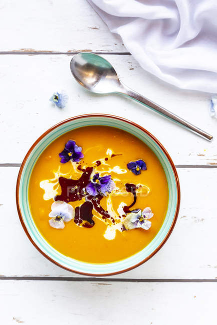 Bowl of creamed pumpkin soup garnished with edible flowers — Stock Photo