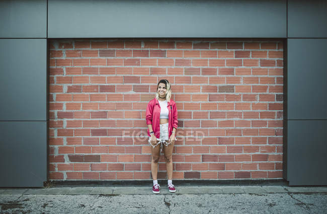 Casual young woman in front of a brick wall — Stock Photo