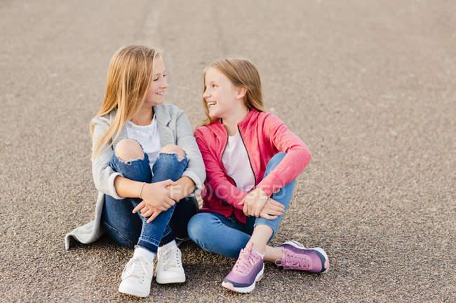 Zwei lächelnde Mädchen, die nebeneinander auf dem Boden sitzen — Stockfoto