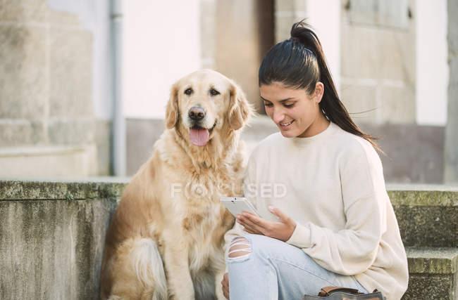 Jeune femme avec son crabot de retriever d'or sur des escaliers à l'extérieur utilisant le téléphone portable — Photo de stock