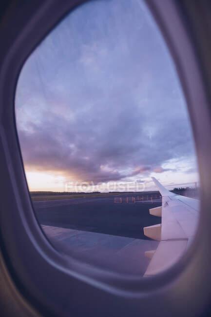Vista da asa do avião através da janela no crepúsculo — Fotografia de Stock