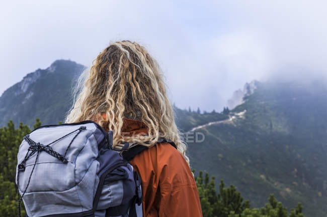 Young woman hiking in the Bavarian mountains, looking at Lake Walchensee — Stock Photo