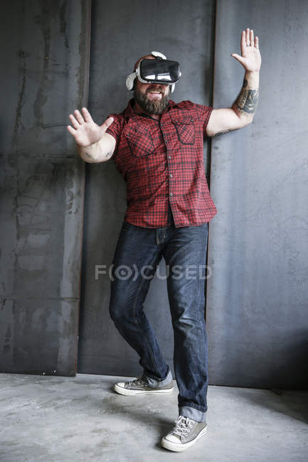 Bearded man wearing VR glasses at grey wall and playing, gesturing with hands — Stock Photo