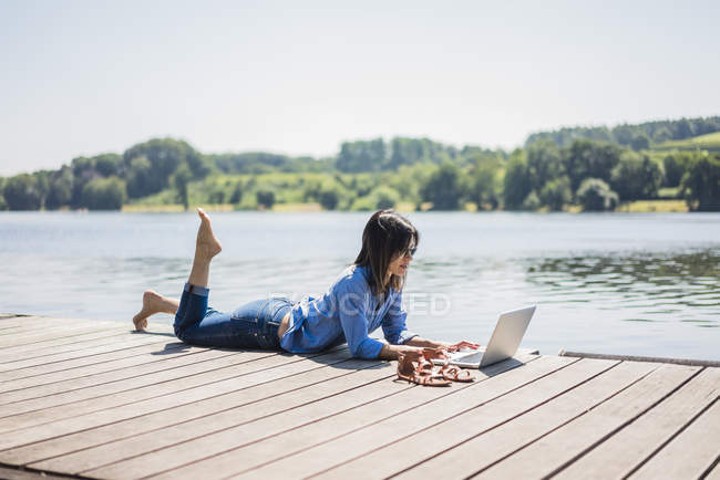 Woman working at a lake, using laptop on a jetty — стоковое фото