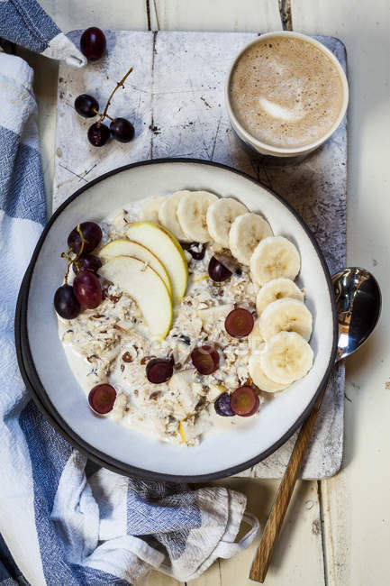 Мюсли миску с бананами, яблоками, виноградом, с кофе — стоковое фото