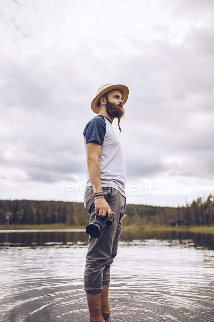 Sweden, Lapland, man with camera standing in water looking at distance — Stock Photo