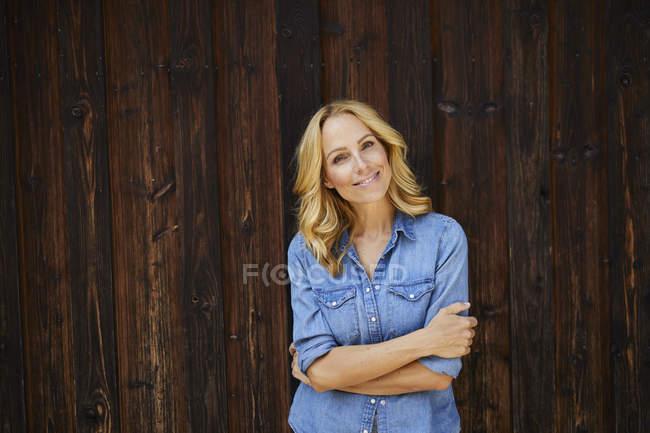 Портрет усміхнена білява жінка перед дерев'яною стіною — стокове фото