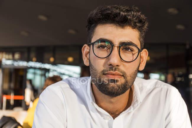 Retrato de joven empresario pensativo con barba y copas en el café de la acera - foto de stock