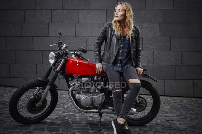 Confident young woman with motorcycle looking away — Stock Photo