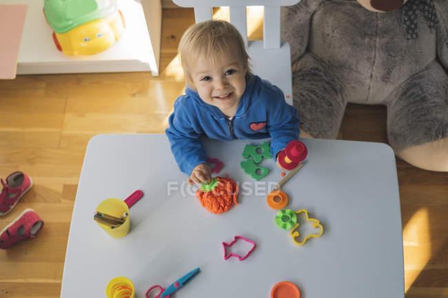 Portrait de bébé fille souriante jouant avec l'argile de modélisation dans la chambre des enfants — Photo de stock