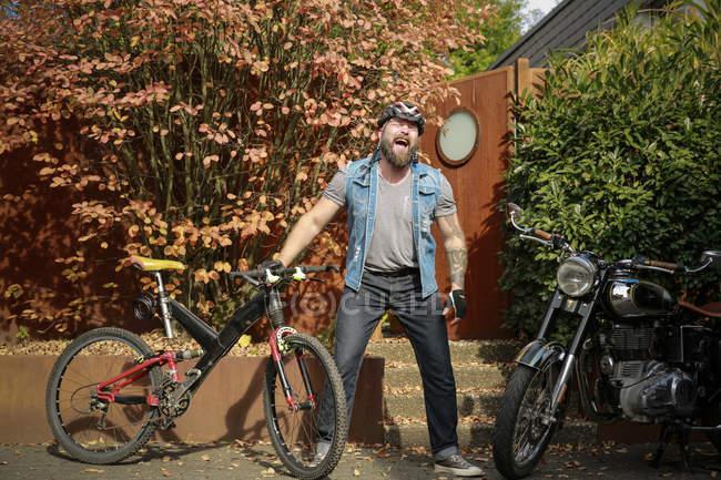 Urla caucasico barbuto uomo in bicicletta casco all'aperto con bicicletta e moto — Foto stock