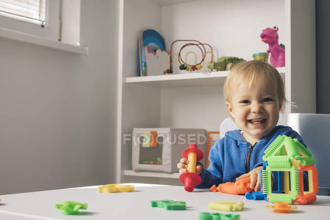 Portrait of laughing baby girl playing with modeling clay in children's room — Stock Photo