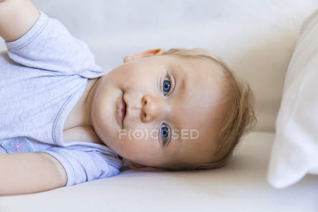 Portrait of blond baby girl lying on couch — Stock Photo