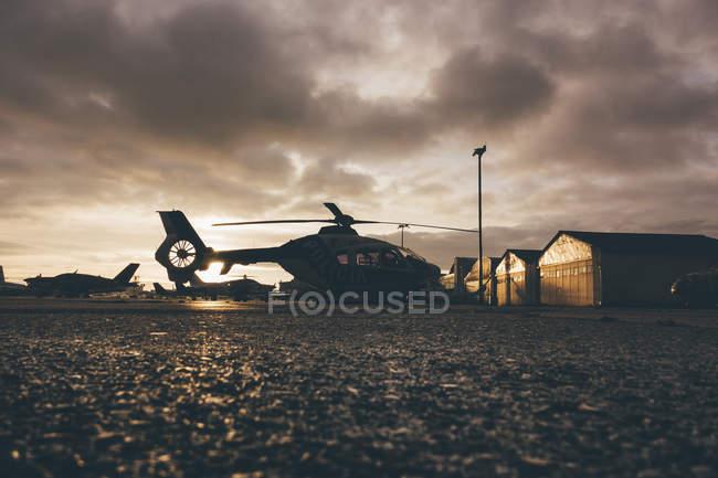 Вертоліт на посадкові місця під час заходу сонця — стокове фото