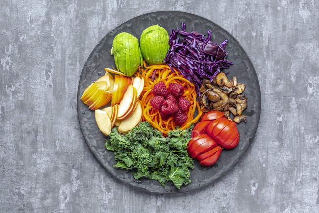Ensalada de aguacate con col roja, tomate, champiñones fritos, zanahoria, manzana y frambuesa - foto de stock