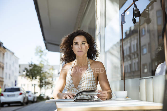 Frau sitzt im Café, liest Buch — Stockfoto