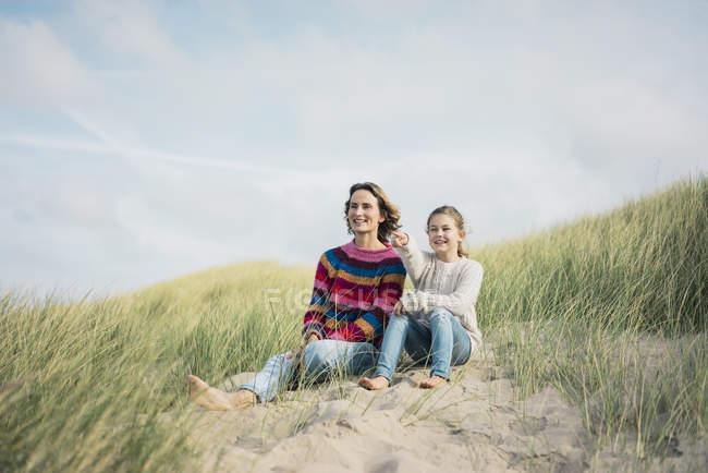 Madre e figlia sedute su una duna da spiaggia, ragazza che indica la distanza, sorridente — Foto stock