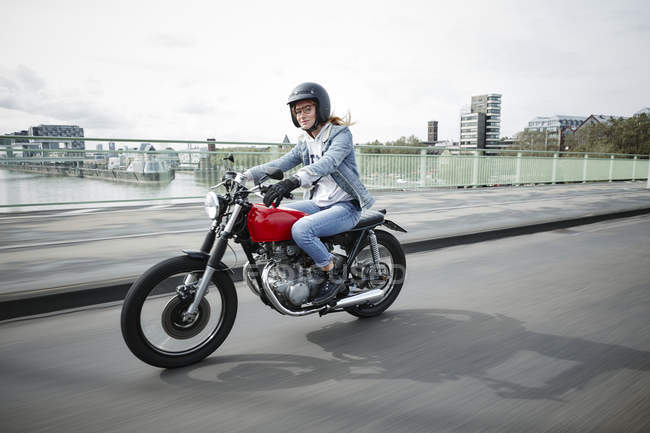 Germany, Cologne, young woman riding motorcycle on bridge — Stock Photo