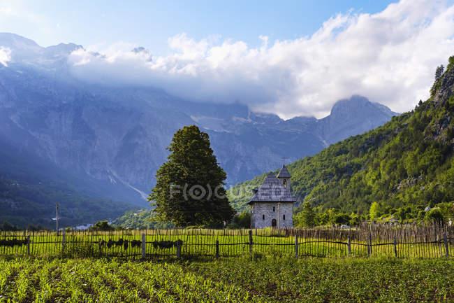 Albania, el condado de Shkoder, los Alpes albaneses, el Parque Nacional Theth, Theth, la Iglesia Católica y los campos - foto de stock