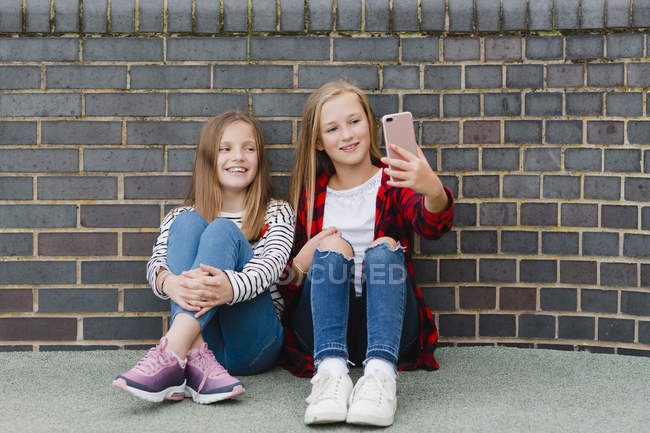 Portrait of two smiling girls sitting in front of brick wall, taking selfie with smartphone — Stock Photo
