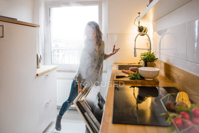 Woman opening steaming dish washer in the kitchen — Stock Photo