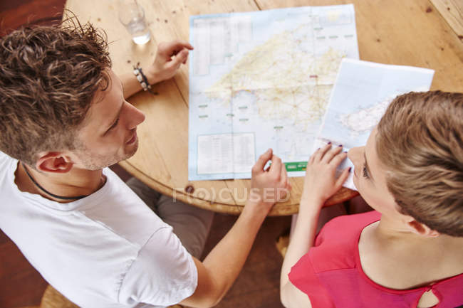 Young couple sitting at table at home with map — Stock Photo