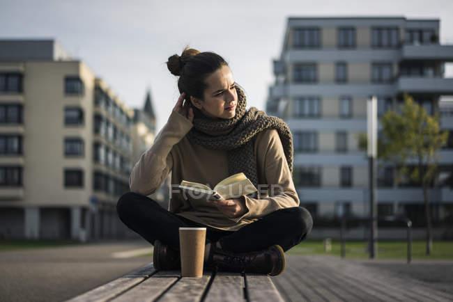 Меланхолія жінка з кавою піти і книга сидячи на лавці восени — стокове фото