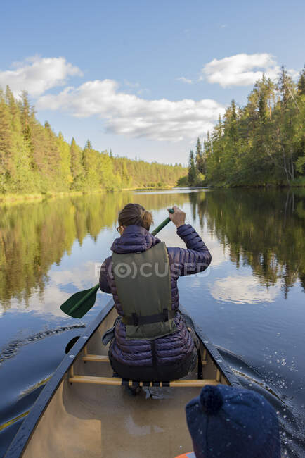 Finlandia, Parque Nacional de Oulanka, mujer en una canoa a orillas del río - foto de stock