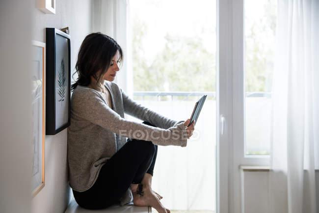 Donna seduta su cassettiera, e-book rosso — Foto stock