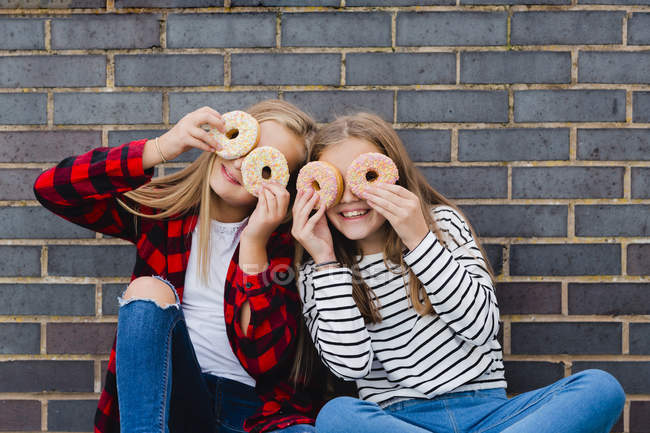 Two girls having fun with doughnuts — Stock Photo