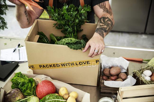Частичный вид человека с доставкой органических овощей в картон, татуировки на руках — стоковое фото