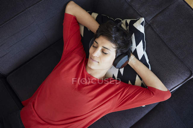 Woman lying on couch at home and wearing headphones — Stock Photo