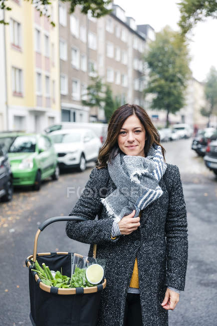 Woman standing in the street, carrying shopping basket with fresh vegetables — Stock Photo