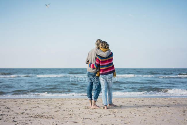 Coppia ture in piedi sulla spiaggia con le braccia intorno, guardando il mare — Foto stock